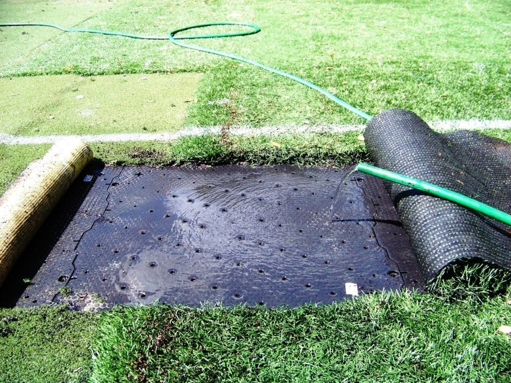 water hose releases water on top of artificial grass base panel