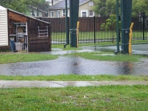rain water pouring out of gutter on flooding soccer field