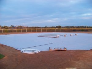 large panels of geo synthetic fabric are laid out on open field for artificial turf installation