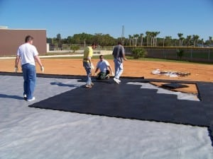 men are installing and walking on base panel system for artificial turf installation