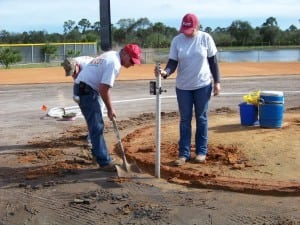 field installers dig area around dirt for base panel system to be placed