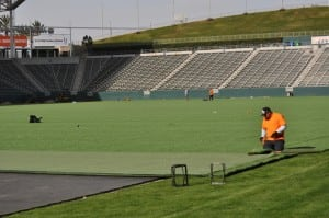 man cutting end of artificial turf on football field