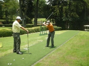 two men putting on an artificial turf tee line