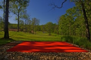red artificial putting green on snag golf course