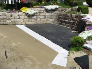 ultrabasesystems panels connected near stone wall for artificial lawn installation