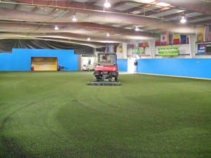 indoor artificial turf field being groomed by truck