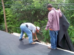 two men laying fabric on the edge of court in a backyard basketball court installation