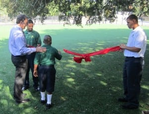 child cuts the ribbon of a newly finished artificial turf soccer field