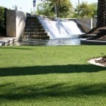 completed artificial lawn turf installation next to waterfall