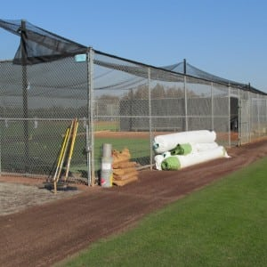rolls of artificial turf rolled up and stacked near fence and installation equipment